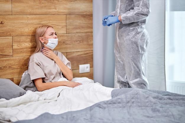 La donna ha sintomi respiratori febbre, tosse, dolori muscolari seduti sul letto a casa parlando con il medico, affetti da una brutta malattia. quarantena, autoisolamento, concetto di assistenza sanitaria