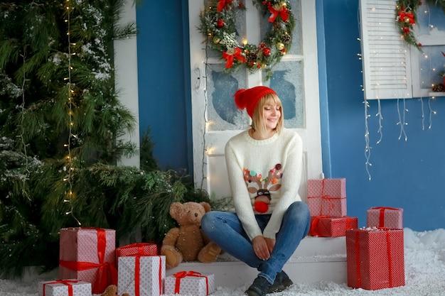 Una donna in un cappello sullo sfondo di scatole regalo di natale rosso e un vero albero di natale verde