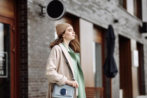 Donna con cappello e cappotto sulla scena del paesaggio urbano per strada