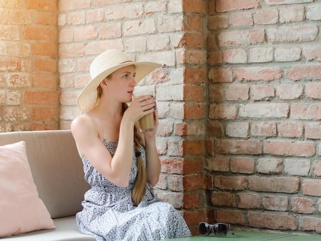Donna con un cappello beve latte in un caffè di strada. viaggi e tempo libero