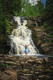 Donna in cappello che gode della natura vicino alla cascata della foresta.