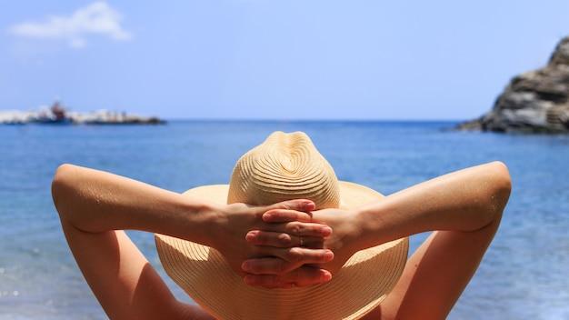 La donna in cappello è sdraiata sulla sedia a sdraio sulla spiaggia dal mare