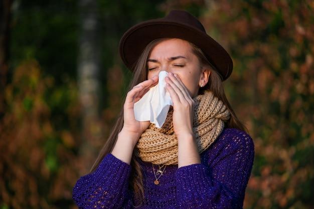 Una donna con un cappello e vestiti a maglia ha preso un raffreddore in autunno e soffre di naso chiuso e che cola e usa un tovagliolo di carta durante gli starnuti all'aperto