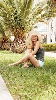 Donna in cappello sotto le palme che si rilassano. isola paradisiaca tropicale, vacanze estive o vacanze. buon umore estivo