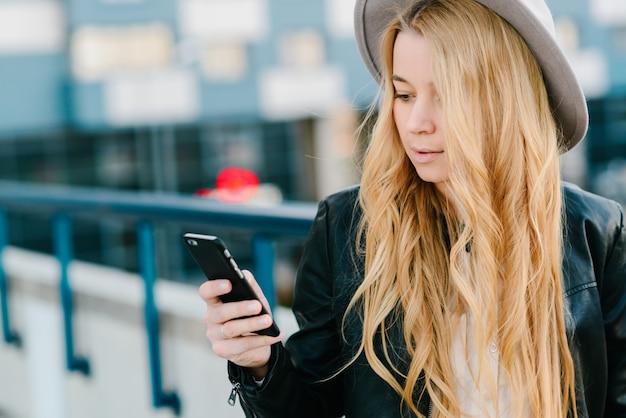 Donna in cappello utilizzando smartphone sulla strada