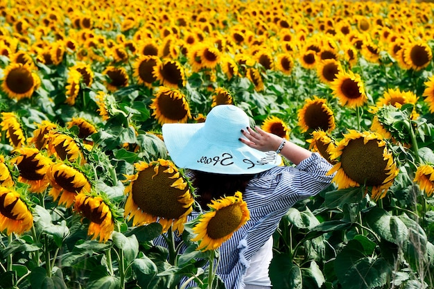 La donna con il cappello dagli ampi margini sta in mezzo a un campo di girasoli
