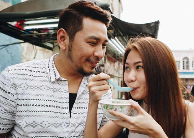 Donna che mangia dessert asiatico all'aperto