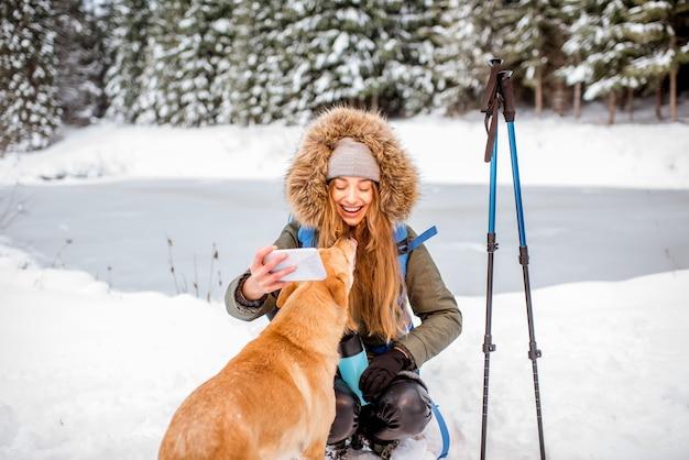 Donna che fa una pausa durante le escursioni invernali facendo selfie con il suo cane sulle montagne innevate vicino al lago e alla foresta