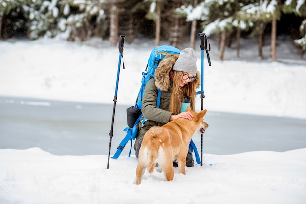 Donna che fa una pausa durante le escursioni invernali accarezzando il suo cane sulle montagne innevate vicino al lago e alla foresta