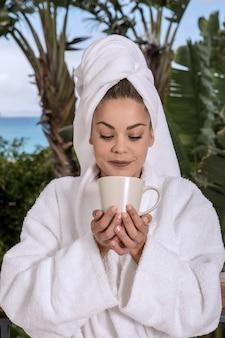 Donna che mangia caffè dopo la doccia