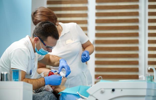 Donna che ha un trattamento dentale presso l'ufficio del dentista. dentista e il suo assistente al lavoro
