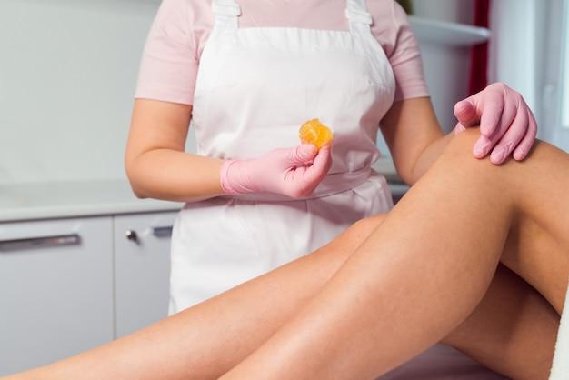 Donna che ha procedura di depilazione sulle gambe con pasta di zucchero in salone