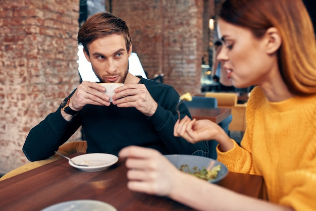 Donna che cena al tavolo di un bar e un uomo con una tazza di caffè in sottofondo