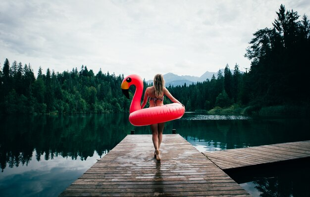 Donna divertendosi con il fenicottero al posto del lago