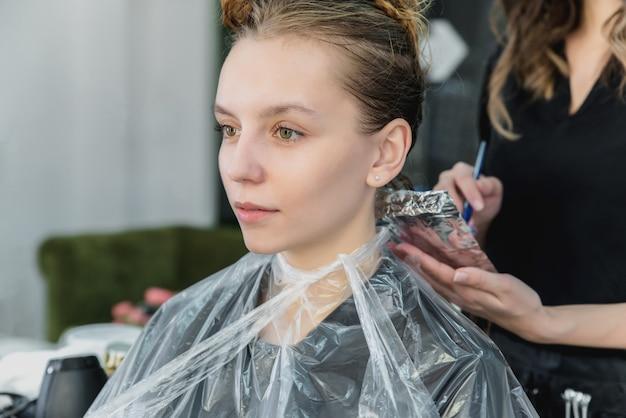 Donna che fa sventare i capelli mentre colora nel salone di capelli