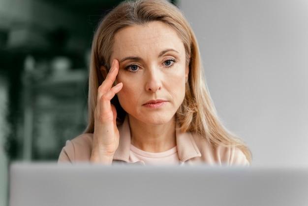 Donna che ha un mal di testa al lavoro