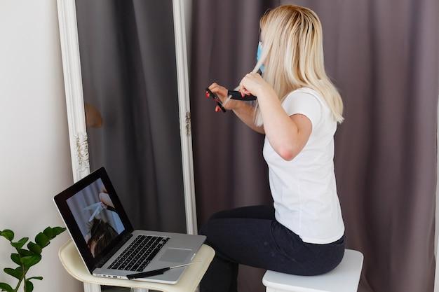 Donna che si fa tagliare i capelli a casa durante la pandemia di coronavirus, , parrucchiere online che impara su un laptop