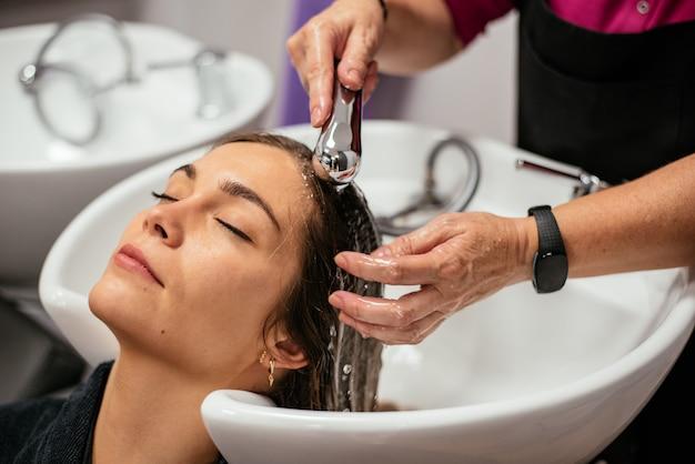 Donna che fa lavare i capelli in un salone
