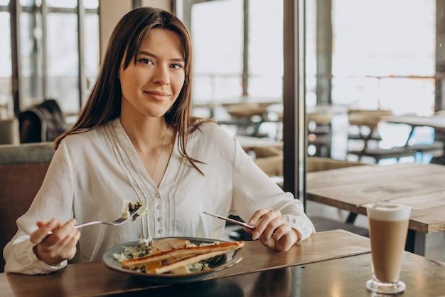 Donna pranzando in un caffè, mangiando insalata