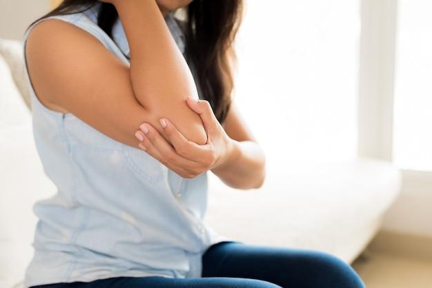 Donna che ha dolore al gomito infortunato. concetto di assistenza sanitaria.