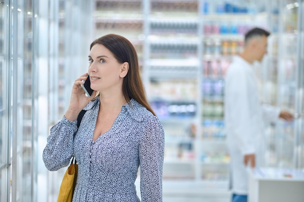 Donna che ha una conversazione telefonica in una farmacia