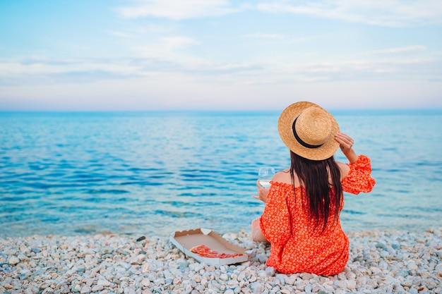 Donna che ha un picnic con pizza sulla spiaggia