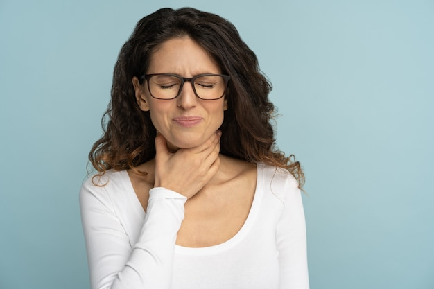 Donna che soffre di mal di gola, tonsillite, deglutizione dolorosa, angina, perdita della voce