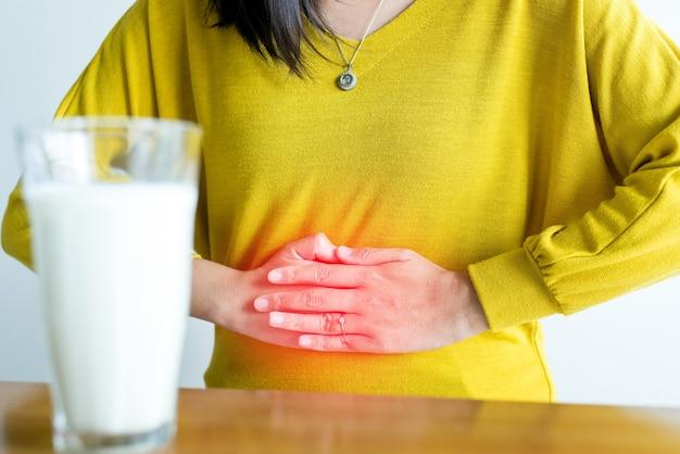 Donna che ha mal di stomaco e un bicchiere di latte, allergia ai latticini, concetto di intolleranza al lattosio