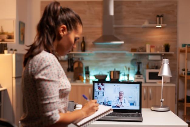 Donna che ha una videoconferenza con il medico a tarda notte e prende appunti. medico che fornisce consulenza al paziente malato dall'ufficio ospedaliero durante l'esame virtuale, il dispositivo, la medicina, l'appuntamento