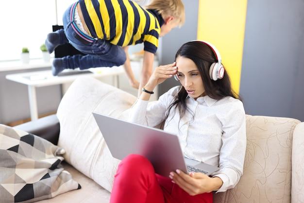 La donna in cuffie e laptop si siede sul divano accanto al bambino coccole