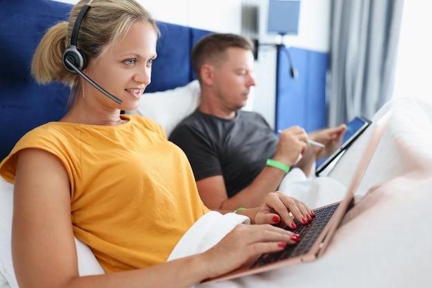 Donna in cuffia sdraiata a letto e lavora al laptop accanto all'uomo con tablet