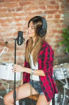 Donna in cuffia che registra musica, canta o fa un tutorial su internet in onda mentre si trova in un loft sul posto di lavoro o a casa. concetto di hobby, musica, arte e creazione. creazione del primo singolo.