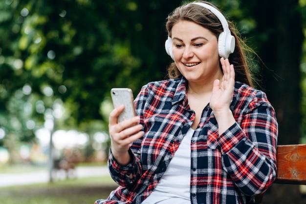 Donna in cuffia, seduto su una panchina, ascoltando qualcosa in cuffia, con in mano uno smartphone