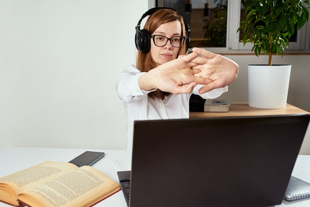 Donna in cuffia che allunga le braccia dopo un lungo lavoro al computer sedentario. lavoro a distanza e concetto di istruzione a distanza.