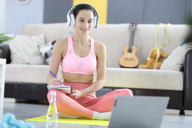 Donna in cuffie e tuta che prende appunti sul taccuino sul concetto di formazione online di perdita di peso. concetto di allenamento fitness online