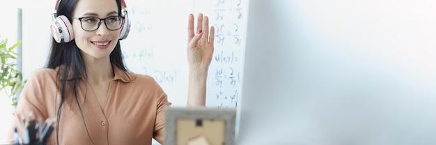 Donna in cuffia che saluta lo schermo del computer