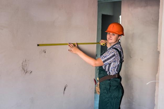 Donna in casco e uniforme protettiva in posa con metro