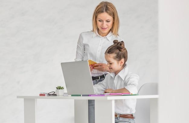 Donna che aiuta sua figlia a fare i compiti al chiuso