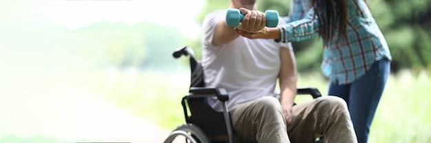 La donna aiuta l'uomo in sedia a rotelle a fare esercizi con i manubri