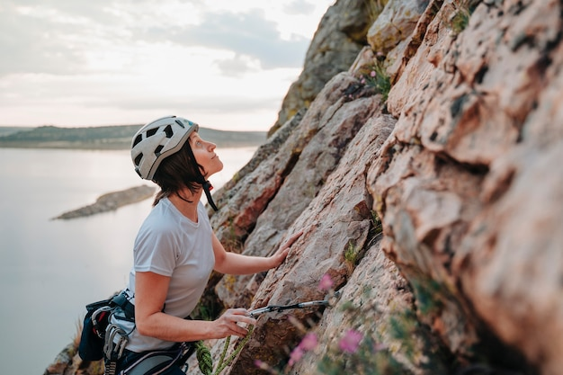 Donna di 30 anni che scala una montagna mentre guarda il tramonto