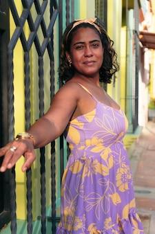 Donna sulla quarantina in abiti alla moda in posa per strada e sorridente.