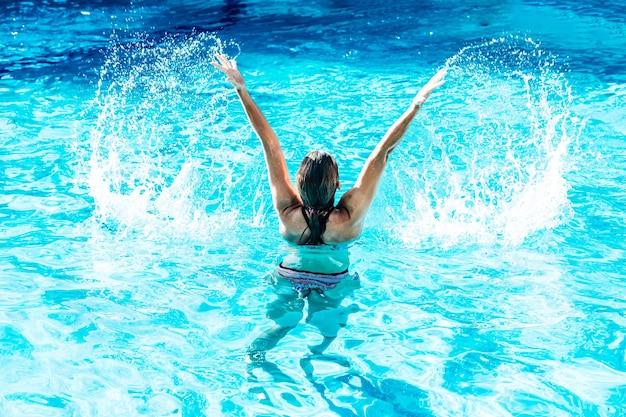 Una donna sulla schiena in una piscina ha sollevato l'acqua con le braccia in un'acqua paradisiaca