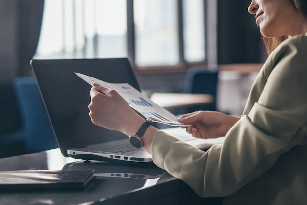 La donna alla sua scrivania sta tenendo un documento e sta esaminando il grafico.
