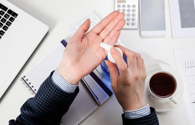 Una donna alla sua scrivania tratta le sue mani con gel antibatterico. donna di affari nel luogo di lavoro con maschera antisettica e protettiva.