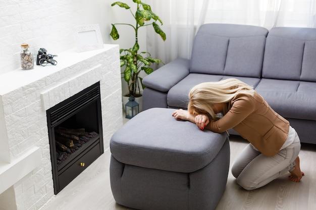 Una donna in ginocchio prega a casa