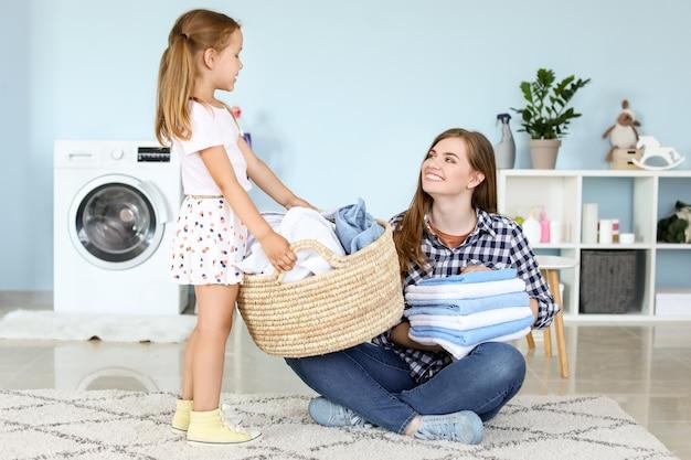 Donna e la sua piccola figlia che fanno il bucato a casa