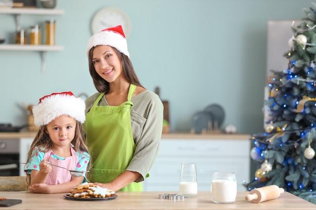 La donna e la sua piccola figlia preparano i biscotti di natale a casa
