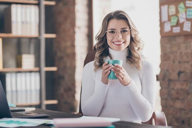 Donna nel suo ufficio a bere caffè