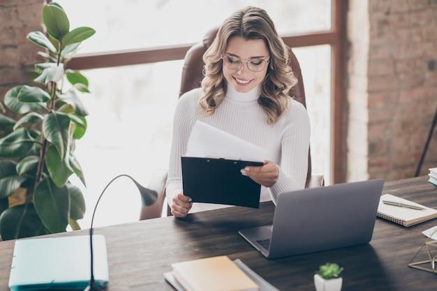 Donna nel suo ufficio che lavora al computer portatile
