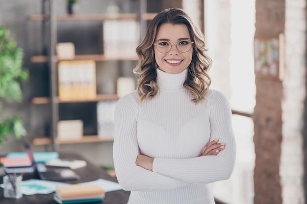 Donna nel suo ufficio che lavora un abito bianco
